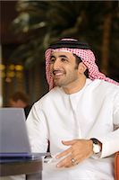 Arab Man Gesturing to Friend in Front of Laptop Computer Stock Photo - Premium Royalty-Freenull, Code: 682-02894169