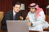 Arab Business Man and Asian Business Man Looking at Laptop Computer Screen Stock Photo - Premium Royalty-Freenull, Code: 682-02894282