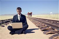 Businessman on a Laptop, Sitting Between Deserted Railroad Tracks Stock Photo - Premium Royalty-Freenull, Code: 682-02894770