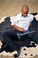 Businessman works on a laptop while sitting on an Nguni cow skin, for luck. Pretoria, South Africa Stock Photo - Premium Royalty-Freenull, Code: 682-02895194