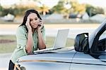 Frustrated Businesswoman Leaning on Hood of Car, Using Laptop Computer and Talking on Cell Phone