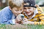 Little Boys Lying on Ground Holding Magnifying Glass