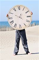 sand clock - Boy Holding a Large Clock on the Beach Stock Photo - Premium Royalty-Freenull, Code: 600-02912548
