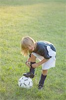 Soccer player tying laces on on football Stock Photo - Premium Royalty-Freenull, Code: 622-02913352