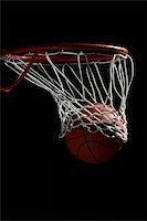 Basketball going through hoop against black background Stock Photo - Premium Royalty-Freenull, Code: 622-02913434