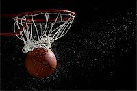 Basketball going through hoop against black background Stock Photo - Premium Royalty-Freenull, Code: 622-02913441