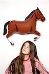Girl with long dark hair standing under plastic horse Stock Photo - Premium Rights-Managed, Artist: F1Online, Code: 853-02913631