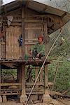 Akha man sitting outside stilted house, Nun Lin Kong village (Akha Tribe), Kengtung (Kyaing Tong), Shan state, Myanmar (Burma), Asia