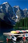 Canoes for hire on shore of Moraine Lake, with view to the Wenkchemna Peaks, Banff National Park, UNESCO World Heritage Site, Alberta, Canada, North America