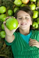 preteen  smile  one  alone - Girl Lying Down on the Ground, Holding an Apple                                                                                                                                                          Stock Photo - Premium Rights-Managednull, Code: 700-02922687