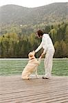 Pregnant Woman on a Dock Playing With Her Dog                                                                                                                                                            Stock Photo - Premium Rights-Managed, Artist: Bettina Salomon          , Code: 700-02922742