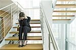 Businesswoman on office staircase holding her head Stock Photo - Premium Royalty-Free, Artist: Glowimages               , Code: 644-02923126