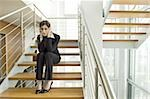 Businesswoman on office staircase holding her head Stock Photo - Premium Royalty-Free, Artist: Cultura RM               , Code: 644-02923128