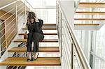 Businesswoman on office staircase holding her head Stock Photo - Premium Royalty-Free, Artist: Siephoto, Code: 644-02923129