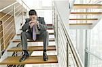 Businessman on office staircase with head on hands Stock Photo - Premium Royalty-Free, Artist: Glowimages               , Code: 644-02923132