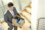 Businessman on office staircase with box of belongings Stock Photo - Premium Royalty-Free, Artist: Cultura RM               , Code: 644-02923137