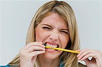 Close-up of a young woman biting a pencil Stock Photo - Premium Royalty-Freenull, Code: 625-02929394