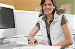 Portrait of a young woman sitting in front of a desktop PC and smiling Stock Photo - Premium Royalty-Free, Artist: Glowimages, Code: 625-02929824