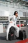 Businesswoman sitting on a suitcase and waiting for a taxi outside an airport Stock Photo - Premium Royalty-Freenull, Code: 625-02929961