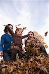 Low angle view of a family playing with leaves Stock Photo - Premium Royalty-Freenull, Code: 625-02930123