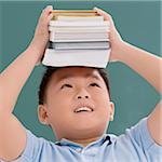 Close-up of a schoolboy holding books on his head Stock Photo - Premium Royalty-Free, Artist: Aflo Relax, Code: 625-02930432