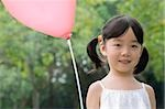 Portrait of a girl with a balloon and smiling Stock Photo - Premium Royalty-Free, Artist: Raoul Minsart, Code: 625-02931858
