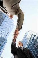 Low angle view of two businessmen shaking hands and smiling Stock Photo - Premium Royalty-Freenull, Code: 625-02932235