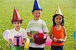 Three children standing together and holding gifts Stock Photo - Premium Royalty-Free, Artist: Raoul Minsart, Code: 625-02932259