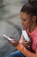 Close-up of a young woman text messaging Stock Photo - Premium Royalty-Freenull, Code: 625-02932457
