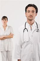 Portrait of a male doctor with a female doctor standing in the background Stock Photo - Premium Royalty-Freenull, Code: 625-02932520