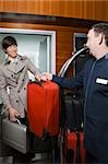 Room service man handing over luggage to a businessman Stock Photo - Premium Royalty-Free, Artist: George Contorakes, Code: 625-02932903