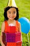 Portrait of a girl holding gifts and smiling Stock Photo - Premium Royalty-Free, Artist: Raoul Minsart, Code: 625-02933066