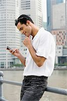 Side profile of a mid adult man text messaging and smiling Stock Photo - Premium Royalty-Freenull, Code: 625-02933176