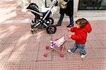 Little Girl Walking With Mother and Pushing Toy Carriage, Madrid, Spain Stock Photo - Premium Rights-Managed, Artist: Mike Randolph            , Code: 700-02935433