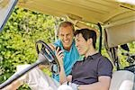 Men in Golf Cart Reading Text Message