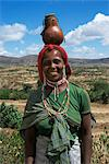 Colourful local woman with beads carrying a gourd on her head, Harer, Ethiopia, Africa