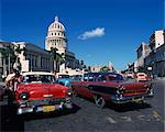 Street scene of old American automobiles used as taxis parked near the Capitolio Building in Central Havana, Cuba, West Indies, Central America