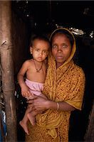 dhaka - Portrait of a Bangladeshi mother in a sari holding her young child, looking at the camera, in a slum in Dhaka, Bangladesh, Asia                                                                          Stock Photo - Premium Rights-Managednull, Code: 841-02947133