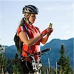 mountain biker stopping to use her cell phone in the middle of the wilderness Stock Photo - Premium Royalty-Free, Artist: Robert Harding Images, Code: 640-02952185