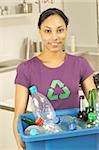 Woman with recycling symbol on t-shirt carrying box with bottles for recycling