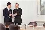 Two businessmen talking in conference room, Munich, Bavaria, Germany Stock Photo - Premium Royalty-Free, Artist: Robert Harding Images, Code: 628-02953600