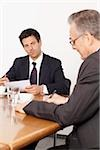 Two businessmen in conference room, Munich, Bavaria, Germany Stock Photo - Premium Royalty-Free, Artist: Blend Images, Code: 628-02953624