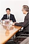 Two businessmen talking in conference room, Munich, Bavaria, Germany Stock Photo - Premium Royalty-Free, Artist: Blend Images, Code: 628-02953649