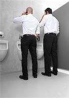 Two businessmen at urinal with cell phones Stock Photo - Premium Royalty-Freenull, Code: 628-02953793