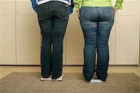 Two full figured women in blue jeans standing on scales (part of) Stock Photo - Premium Royalty-Freenull, Code: 628-02954517