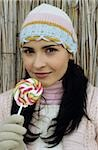 Darkhaired young Woman with a crocheted Hat holding a Lollipop - Sweets - Season Stock Photo - Premium Royalty-Freenull, Code: 628-02954662