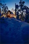 Cabin lit at dusk with snow covered trees Alaska   winter spruce birch