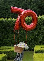 Red inflatable balloon in the shape of the number seventy attached to a bycycle parked in a garden                                                                                                       Stock Photo - Premium Rights-Managednull, Code: 822-02958486