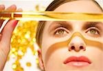 Close up of a young woman face holding a golden glass tube over her face                                                                                                                                 Stock Photo - Premium Rights-Managed, Artist: ableimages               , Code: 822-02958564
