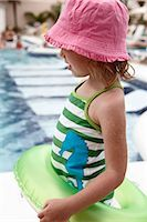Little Girl With Inner Tube Playing on Pool Deck Stock Photo - Premium Royalty-Freenull, Code: 600-02967521